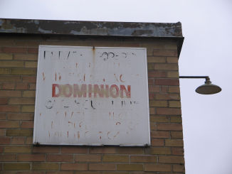 [Decades-old Dominion sign still clinging to the wall of what was once a store]